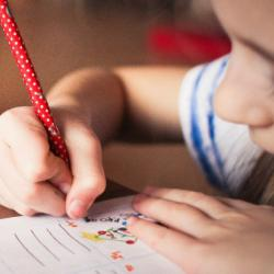 Child drawing with coloured pencils