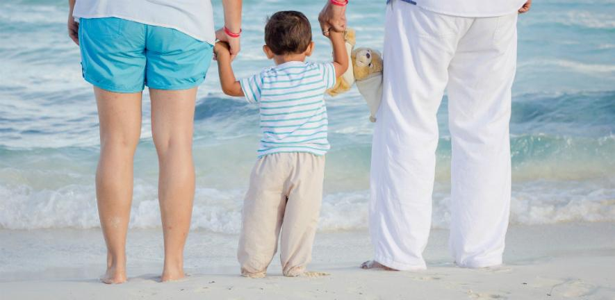 photo of toddler holding parents' hands on the beach